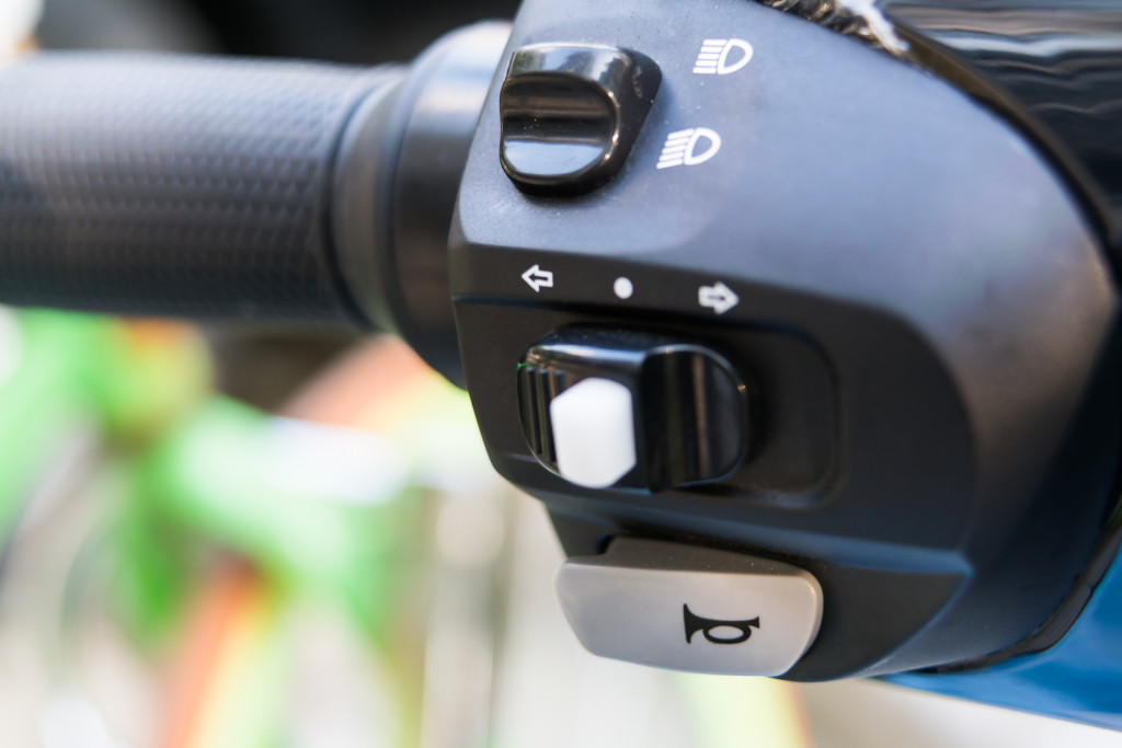 closeup the motorcycle horn and switch off/on lighting on e-bike handle bar