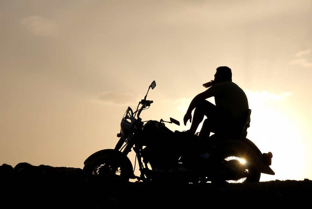 """A man is sitting on a motorcycle, watching the setting sun and drinking his whiskey"""